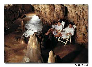 A couple absorbs the vapors of the natural spring in the grotta.