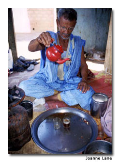 A man ceremoniously pours tea.
