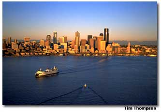 This aerial view of the Seattle skyline is flanked by Puget Sound on one side and the Cascade mountains on the other.