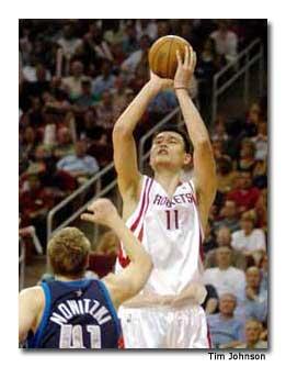 Ming shoots past Dallas' Dirk Nowitzki.