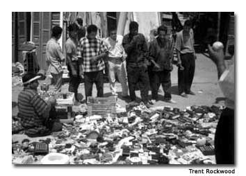 """Tourists and local residents gather at the """"Friday Market"""" to do some bargain shopping."""