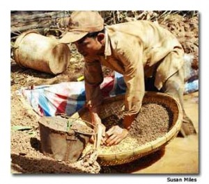 A gem stone miner sorts through the slush pit in