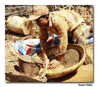 A gem stone miner sorts through the slush pit in
