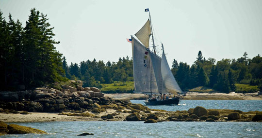 A Maine Windjammer cruises through a narrow passage in Maine.