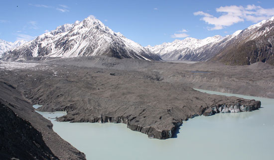 Tasman Glacier Terminal Lake from atop a mountain, with blackened glacial tongue. Photo by Richard Varr.