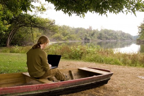 A man is working with his notebook in outdoors