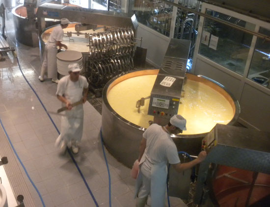 Cheese makers stir huge kettles of cheese at La Maison du Gruyère in Switzerland.