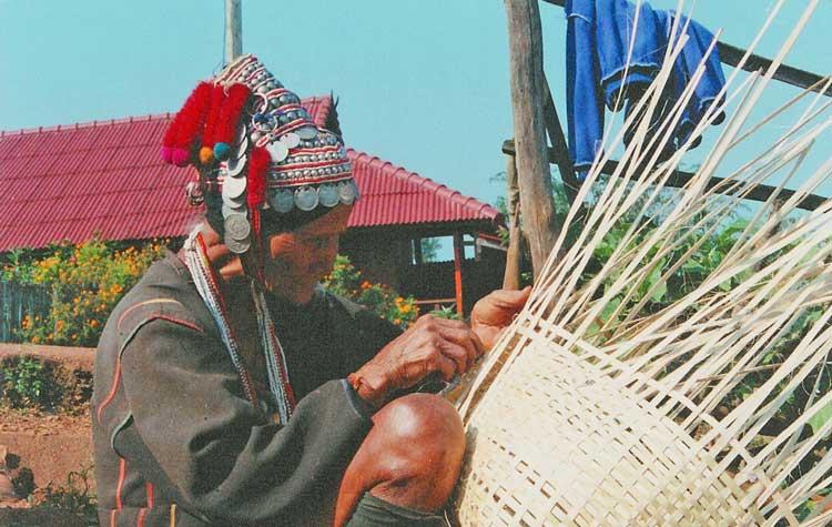 Akha woman weaving a basket in Thailand
