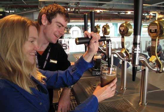 Austin Peavoy shows author Amy Laughinghouse how to pour the perfect pint at the Guinness Storehouse, which produces three million pints of Guinness a day. Photo by Shareen Gustafson Newman.
