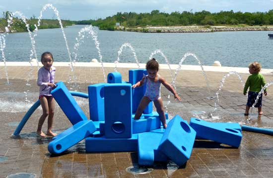 Children love cooling off in the fountains at Camana Bay.