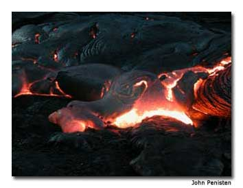 A surface lava flow glows at night.