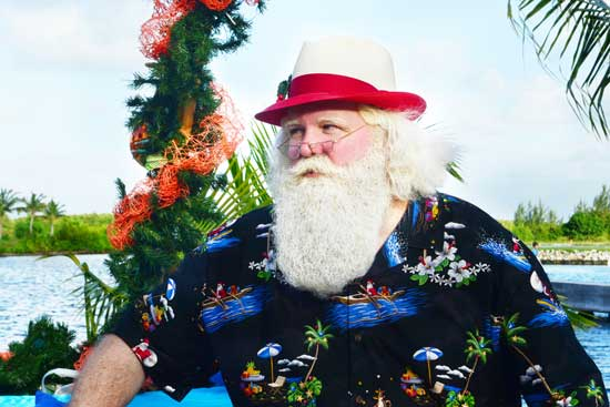 Caribbean Santa greets guests on an island in Camana Bay. Photo credit: Camana Bay