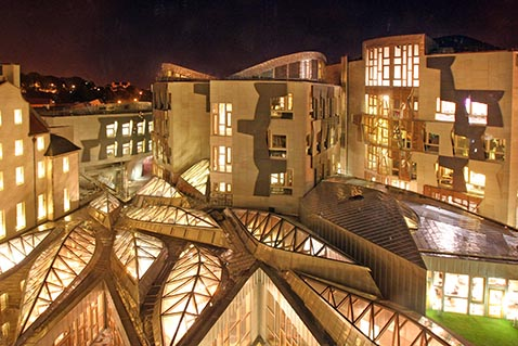The Scottish Parliament lit up at night, as seen from above.