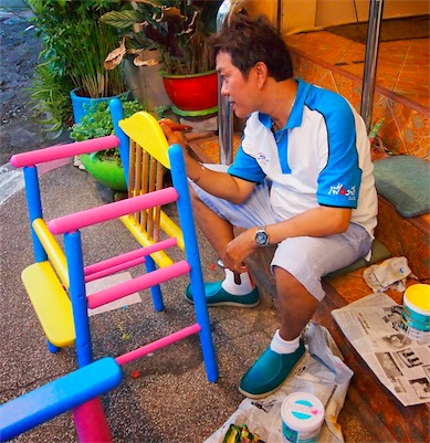 A hardworking business owner painting a chair in bright colors. Photo by Arman Shah/Asiarooms