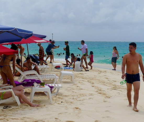 Divers take a break on the beach at nearby Johnny Caye. Photo by Bob Schulman