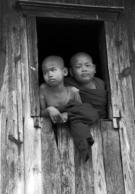 A pair of young monks look out the window of a home near the remote hill side town of Kalaw in central Myanmar. Photo by Pamela Roth