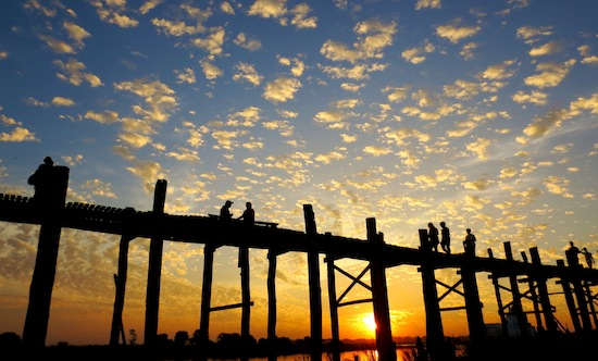 Pedestrians make their way across the U Bein Bridge near the City of Mandalay. At 1.2 km, it's the longest teak bridge in the world. Photo by Pamela Roth