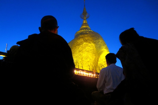 Monks gather around the famed Golden Rock and say their prayers in southeast Myanmar. Photo by Pamela Roth