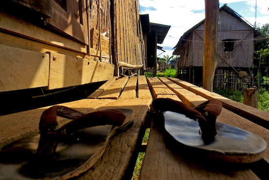 A pair of warn out flip flops sit on the steps of a home built on stilts in one of the villages along Inle Lake in central Myanmar. Photo by Pamela Roth