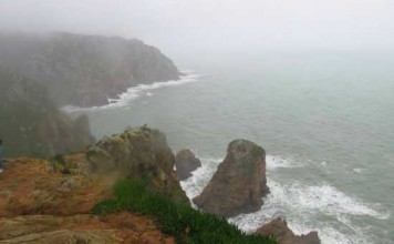 Waves crashing into the Cabo Da Roca cliffs, breaking the stillness of the ocean. Photo by Monica Gray