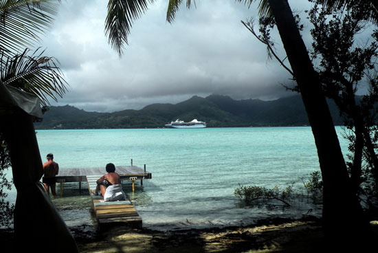 Cruise ship Paul Guauguin in the distance. Photo by Annie Palovcik