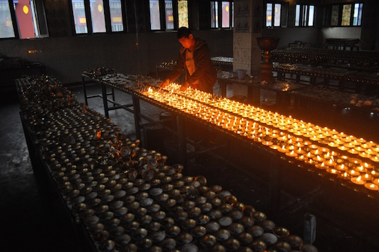 A Buddhist monk lights butter lamps in Sherabling Monastery, Himachal Pradesh. Lighting of butter lamps in Buddhist monasteries is a ritual, performed with divine incantations.