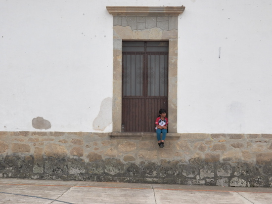 A child sitting in one of the stone windowsills in San Sebastian, Mexico. Photo by Cynthia Pulido