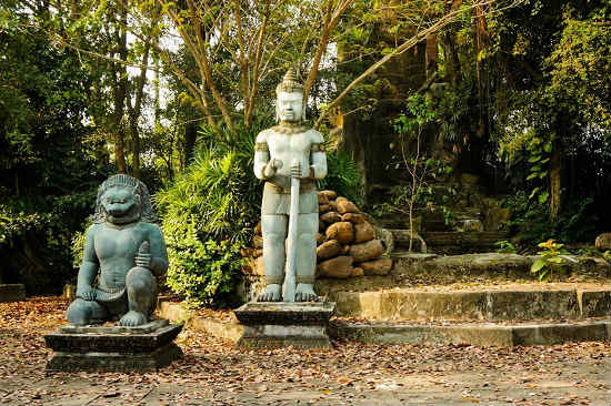 Two carved statues are nestled in the forest.