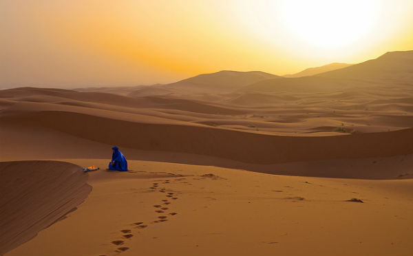 The Sahara at dawn lights up golden with the sunrise.