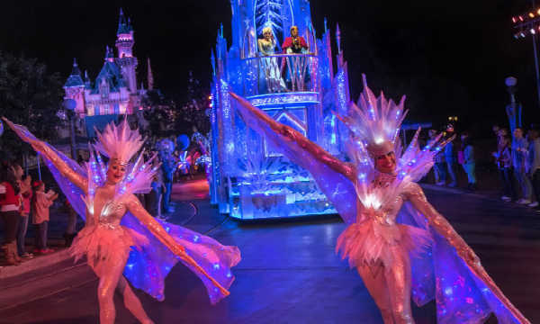The parade shimmers and glows as children delight in the chance to see Frozen characters.