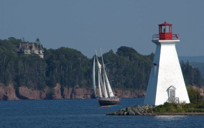 Touring sail boat passes the lighthouse at Baddeck on the Bras d'Or Lake. In the background is the former summer home of Alexander Graham Bell.