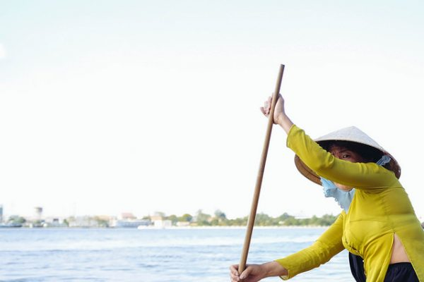 A woman paddles on the Mekong. Photo by Flickr/hadi