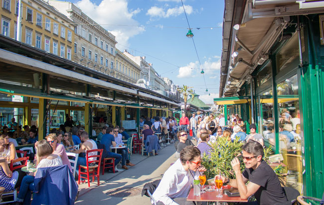 Diners enjoy the sun at one of the restaurants at the Naschmarkt in Vienna. Photo by Janna Graber
