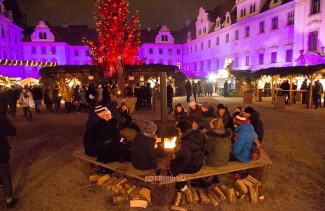 Friends gather round a fire at the Romantic Christmas Market in Regensburg, Germany. Photo by Benjamin Rader