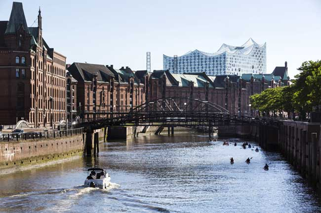 The Elbphilharmonie stands tall in the distance from Speicherstadt. Photo by Jorg Modrow, Hamburg Tourism