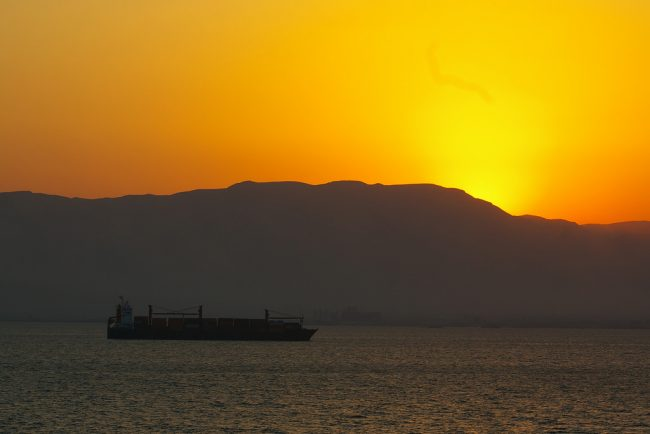 A container ship moves along the Suez Canal at sunset. Flickr/Tim