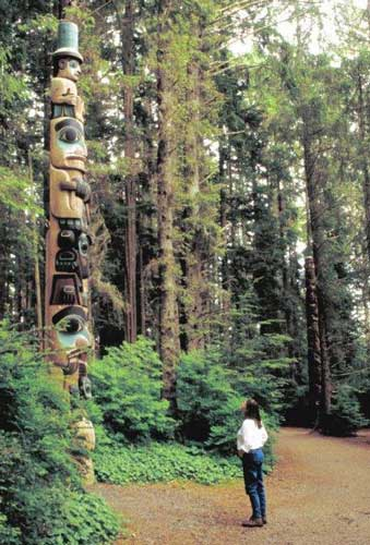 Admiring a totem pole in Alaska. Photo by Victor Block