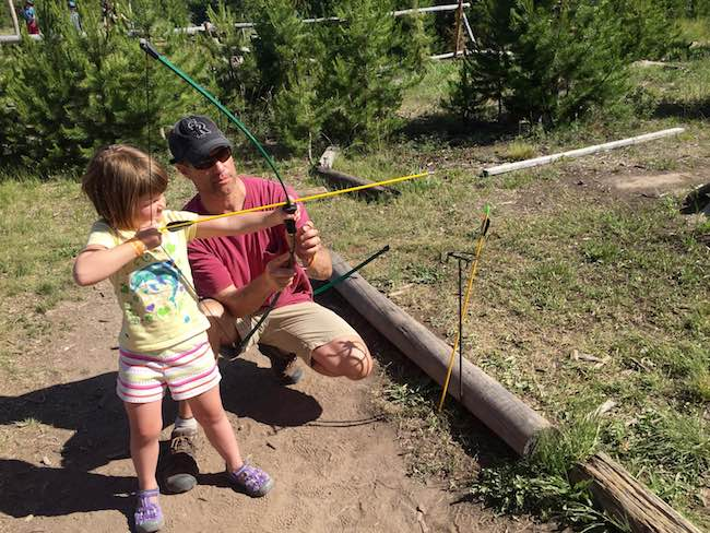 Learning the fine art of archery from dad. Photo by Claudia Carbone