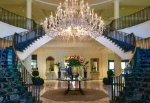 "Classic Southern ""Open Arm"" staircase showcases crystal chandelier in the marble lobby. Photo by Claudia Carbone"