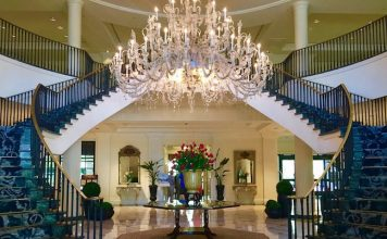 """Classic Southern """"Open Arm"""" staircase showcases crystal chandelier in the marble lobby. Photo by Claudia Carbone"""