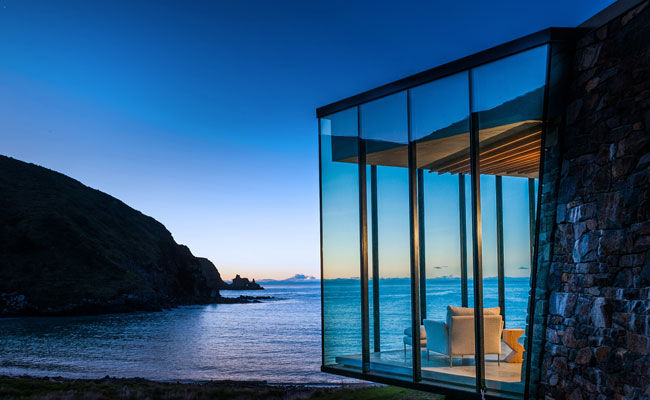 Guests arrive by helicopter at Seascape Annandale on Banks Peninsula to a James Bond-like setting with accommodations that appear to be floating over the open sea.