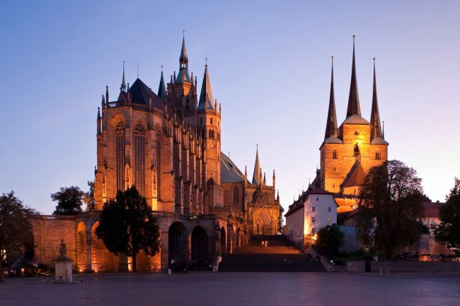 Two magnificent Catholic churches stand on a hill overlooking the central square in Erfurt. The one on the left is St. Mary's Cathedral and is the place where Martin Luther was ordained. The three-towered structure on the right is St. Severus Church. (Photo credit: Toma Babovic — Thüringer Tourismus GmbH)