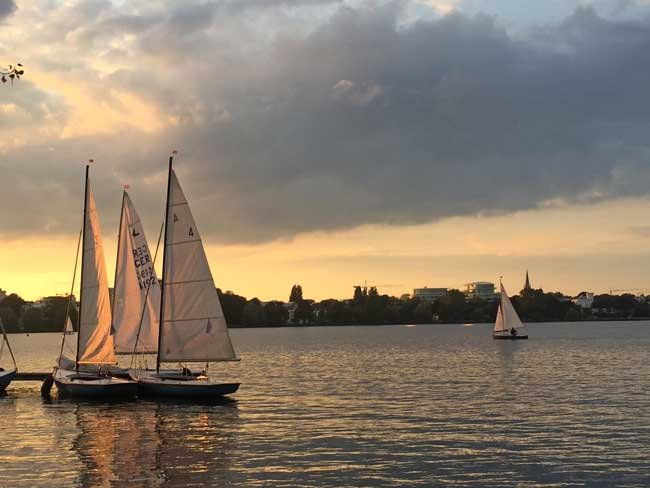 Sailboats at sunset on Alster Lake in Hamburg. Photo by Janna Graber