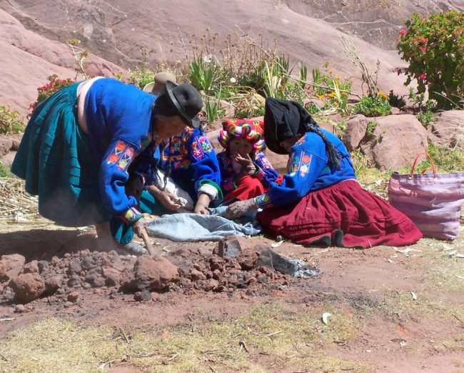 The Aymara women tended an underground oven, where plump rounded potatoes sizzled for our lunch. Photo by Carol L. Bowman