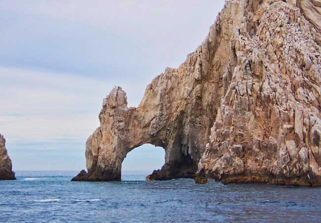 Massive granite rocks welcome cruise ships to Cabo San Lucas at the southern tip of the Baja Peninsula where the Pacific Ocean meets the Sea of Cortez.