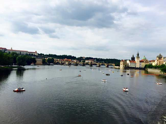 View of the Charles Bridge in Prague during mid-spring. This time of year brings warmer weather and the opportunity to paddleboat on the Vltava River.