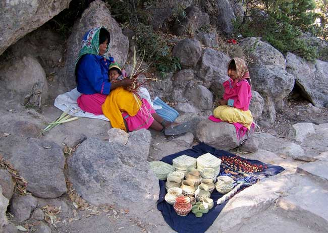 Tarahumara women wait patiently with their children to sell their baskets to travelers. Photo by Carol L. Bowman