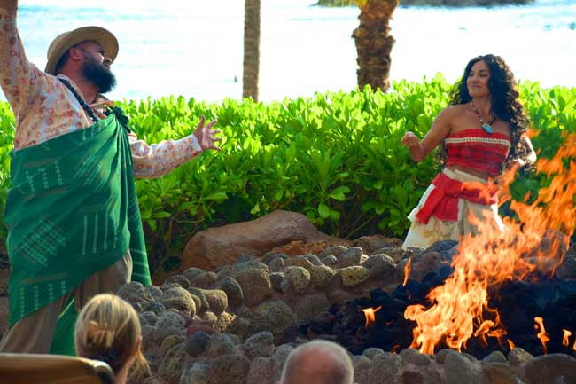 Uncle and Moana share island tales with guests around a campfire. Aulani, A Disney Resort and Spa.
