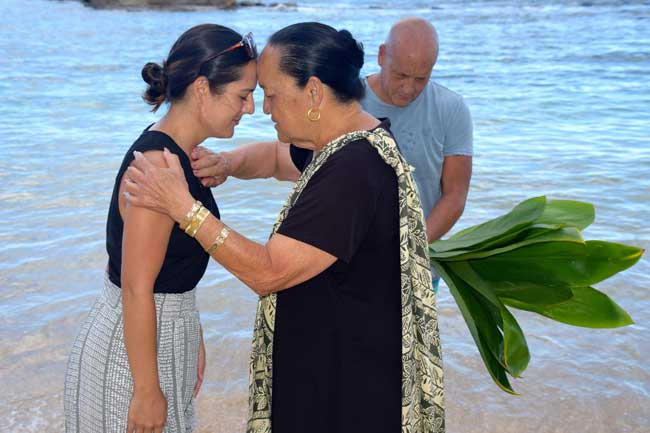 Kahu Auntie Nettie blesses a guest at Lanikuhonua Beach in front of the Four Seasons Resort.