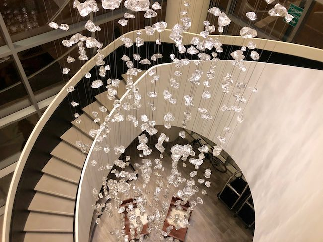 Chandelier in stairway. Photo by Claudia Carbone